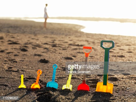 Row of assorted plastic spades standing in sand : Stock Photo
