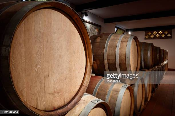 Row of barrels emerging from darkness in a wine cellar