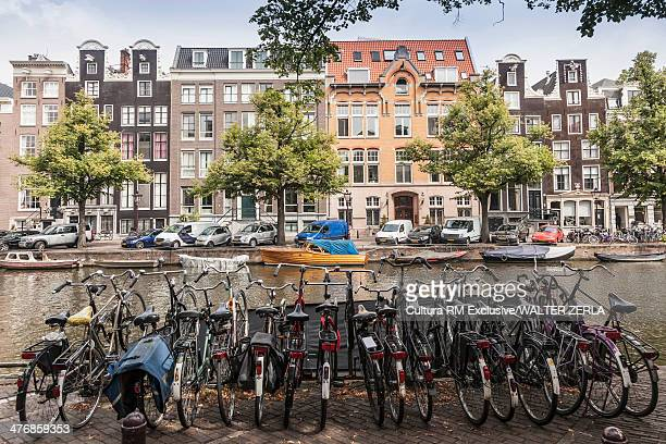 Row of bicycles parked next to canal, Amsterdam, Netherlands