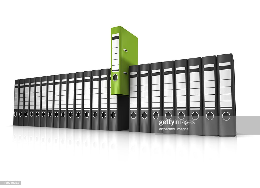 A row of black lever arch files, and one green one : Stock Photo