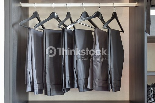 row of black pants hangs in wardrobe at home : Stock Photo
