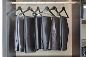 row of black pants hangs in wardrobe at home