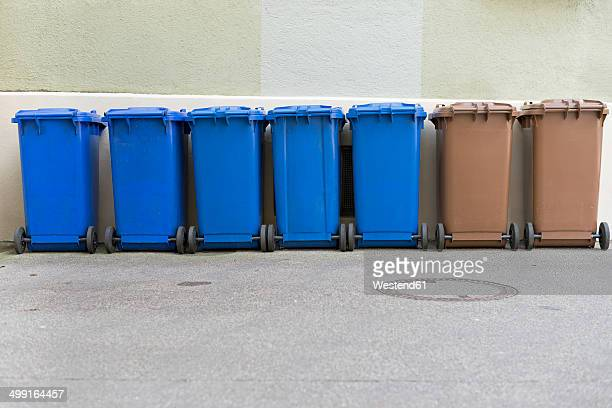 Row of blue and brown garbage cans