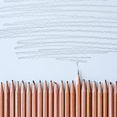 Row of blunt, worn wooden drawing pencils on a white drawing paper background with one wooden pencil that is extremely sharp standing out from the crowd in contrast to the blunt pencils, with a pencil