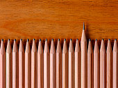 Row of blunt, worn wooden drawing pencils on a wood background with one wooden pencil that is extremely sharp standing out from the crowd in contrast to the blunt pencils. Good copy space. Concept rel