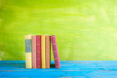 row of books, free copy space, on green background