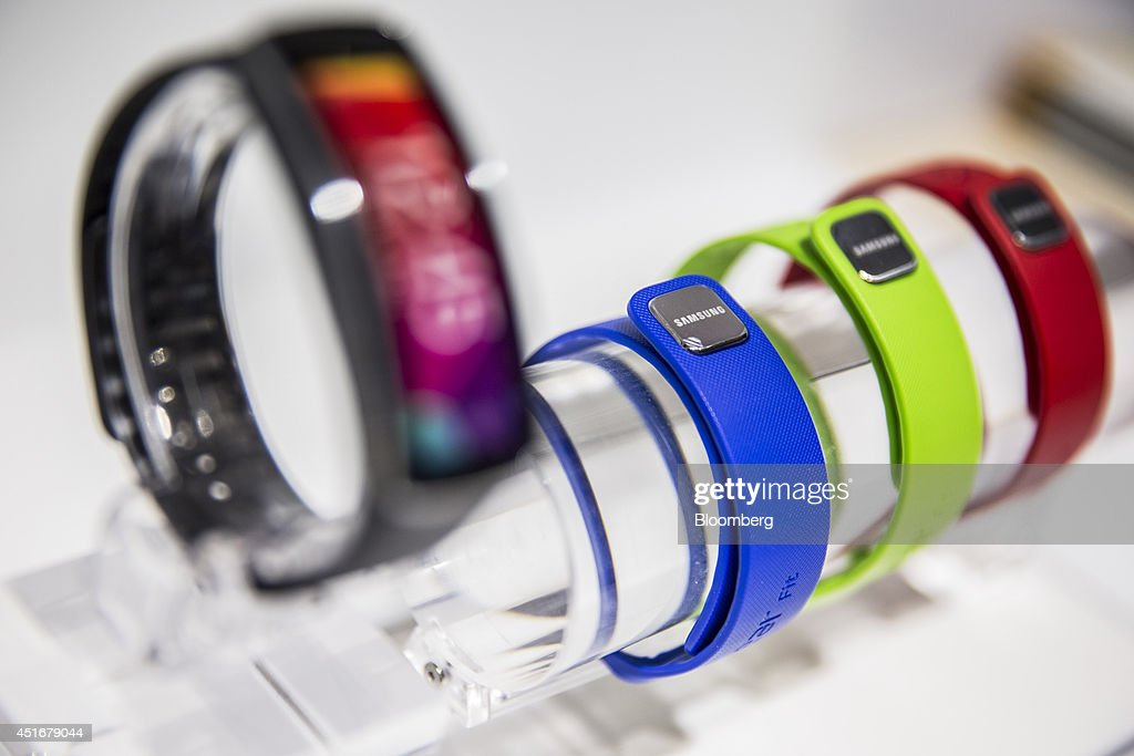 A row of brightly colored Samsung Galaxy Gear Fit smartwatches, manufactured by Samsung Electronics Co., are displayed for sale inside a Bouygues Telecom store, operated by Bouygues SA in Paris, France, on Thursday, July 3, 2014. Bouygues Telecom, France's third-largest mobile operator, was looking for a buyer as profitability and cash generation declined. Photographer: Balint Porneczi/Bloomberg via Getty Images