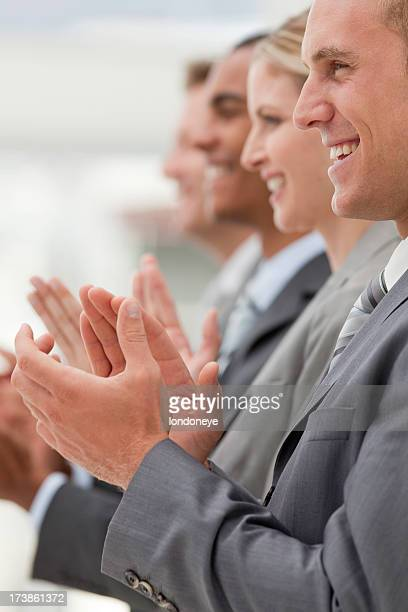 Row of business professionals clapping.