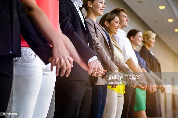 Row of businesswomen and men holding hands in office