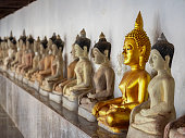 Row of cement Buddha images in a surrounding cloister around a Thai Buddhist temple, with one Buddha image painted in gold, standing out from the crowd of other cement colored Buddha images in the lin