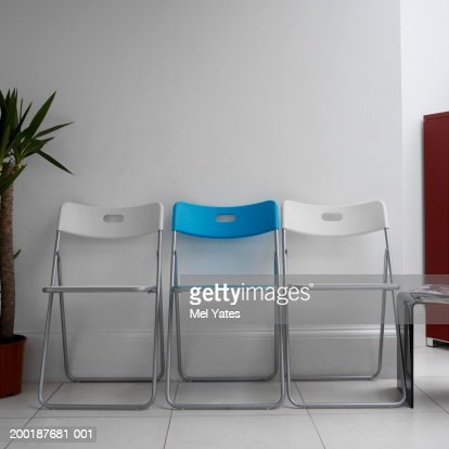 Row of chairs against wall in waiting room