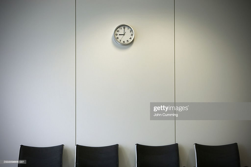 Row of chairs below wall clock in office waiting area