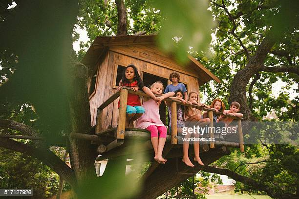 Row of children sitting on a rustic wooden treehouse porch