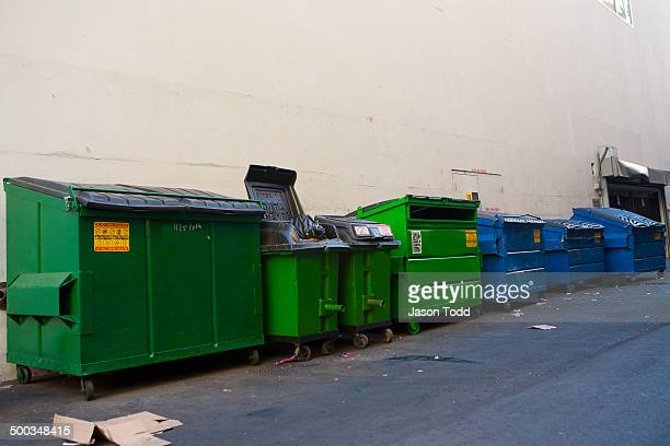 Row of city garbage dumpsters in alley