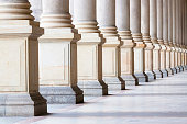 Closeup bases row of marble columns. Symbols of integrity, stability, and trustworthiness. Closeup row of classical marble columns. Detail of Mlynska colonnade Karlovy Vary Czech republic establish 18