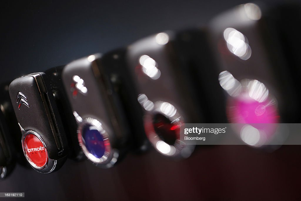 A row of colored key fobs for Citroen automobiles, produced by PSA Peugeot Citroen, are seen on display on the first day of the 83rd Geneva International Motor Show in Geneva, Switzerland, on Tuesday, March 5, 2013. This year's show opens to the public on Mar. 7, and is set to feature more than 100 product premiers from the world's automobile manufacturers. Photographer: Valentin Flauraud/Bloomberg via Getty Images
