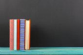 Stack of colorful hardback books, open book on black board background