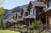 Image of the front porches on a row of condominiums in historic downtown Durango, Colorado.  Behind the homes, the cliff of Smelter mountain can be seem.  The many repeating identical homes are typica