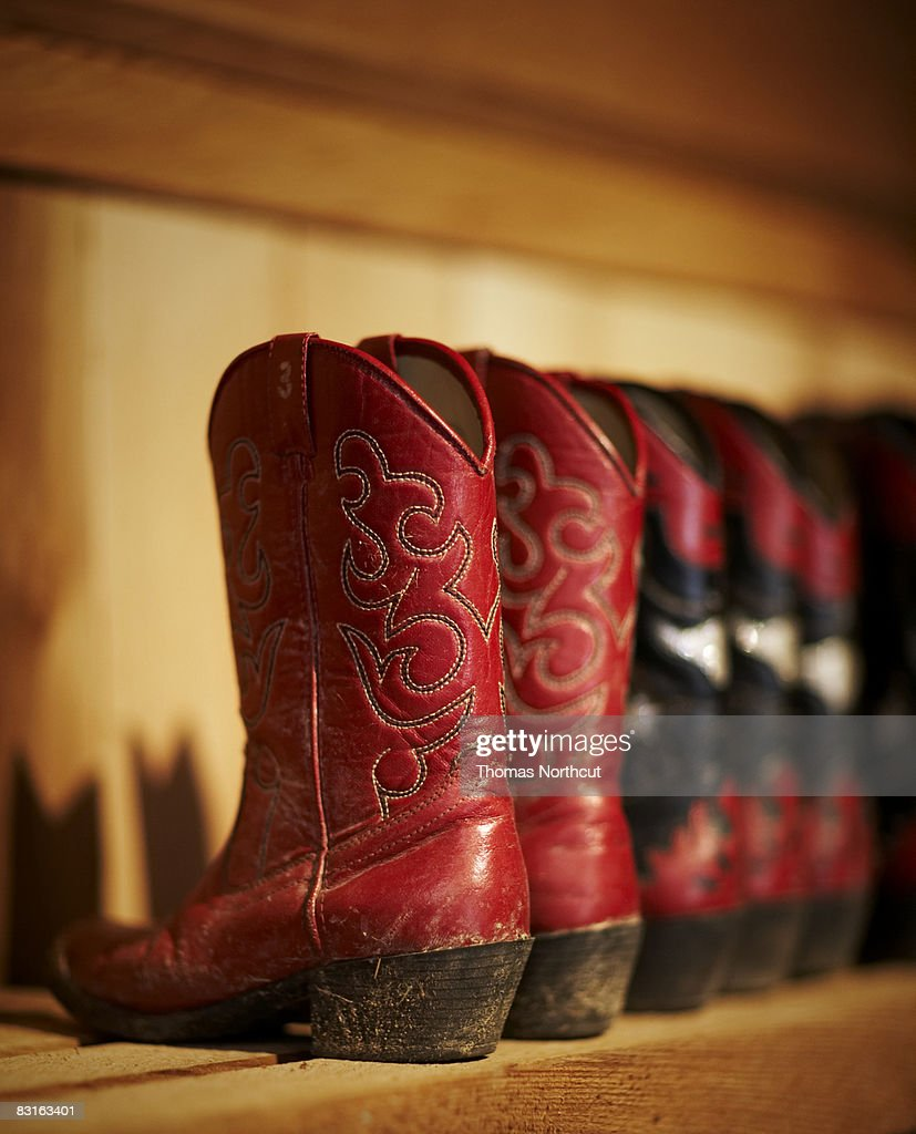 Row of cowboy boots sitting on a shelf : Stock Photo