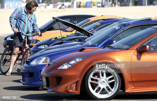 A row of customized imports draws the interest of a passerby during Saturday's Sports Car Club meeting at the Santa Monica Pier The event publicized...