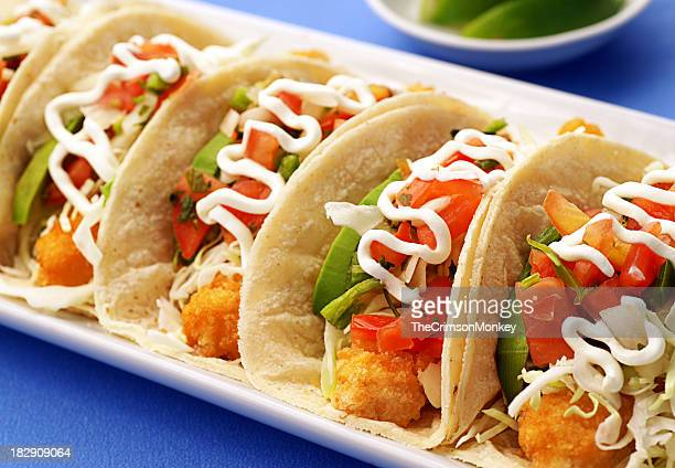 A row of delicious fish tacos on a plate