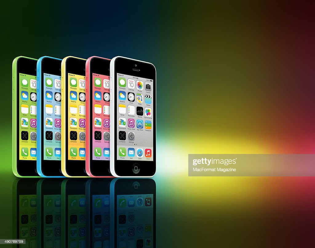 A row of different coloured Apple iPhone 5C smartphones photographed on a rainbow background, taken on September 20, 2013.