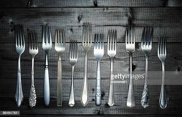 Row of different forks on wood