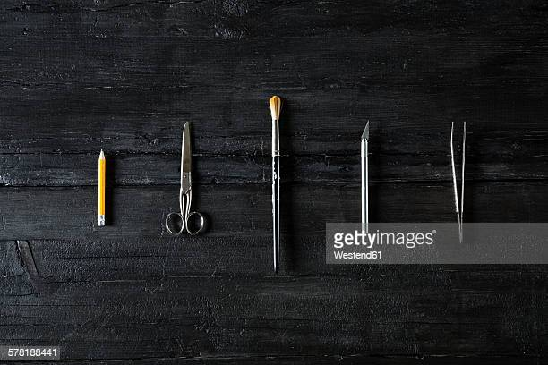 Row of different tools on black wood