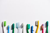 row of different toothbrushes, on white with copy space