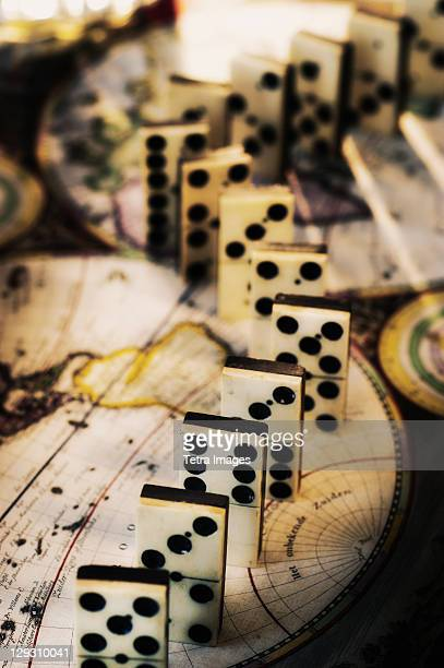 Row of dominoes on old world map