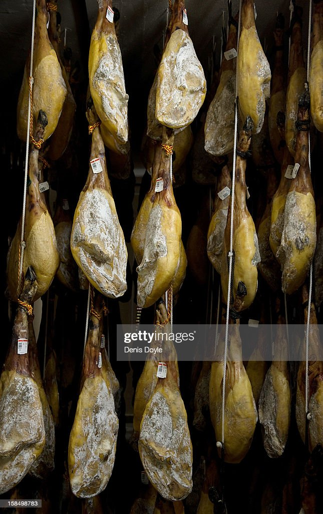 A row of dry-cured Jamon Iberico de Bellota (acorns) hang at the Estrella de Castilla factory in the town of Guijuelo on December 14, 2012 near Salamanca, Spain. Dry-cured Iberian ham or Jamon Iberico de Bellota is a favourite amongst Spaniards and producers are hoping for improved sales over the busy christmas period. The jamon Iberico de Bellota are usually dry-cured for up to three years after the pigs have been few on a diet of acorns in the last three months of their lives.