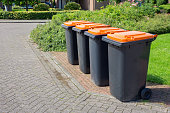 Row of european grey waste bins along street. In the netherlands we collect our garbage in separate containers. These grey ones with orange lids are filled with plastics, cans and packs for fluids. We