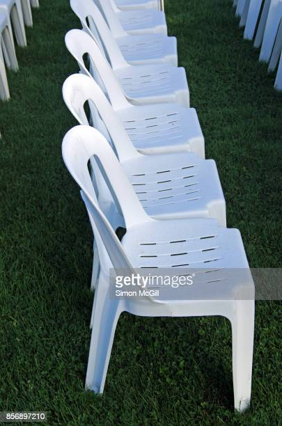 Row of empty white plastic chairs arranged in readiness for an outdoor event