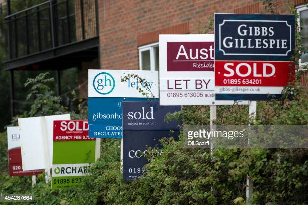 A row of estate agent boards are placed outside sold and let properties on August 28 2014 in London England A report from the Department for...