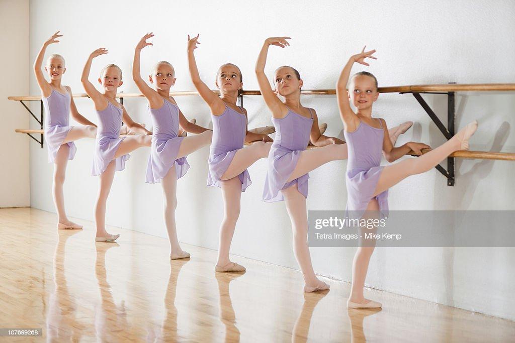 Row of female ballet dancers (6-7,8-9) in dance studio