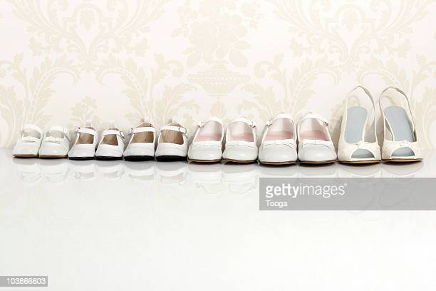 Row of female shoes from baby  to adult high heels