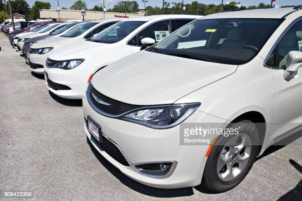 A row of Fiat Chrysler Automobiles 2017 Crysler Pacifica minivan vehicles are displayed for sale at a car dealership in Moline Illinois US on...