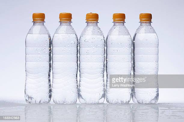 A row of five full plastic water bottles in a row