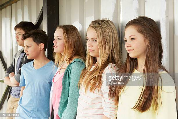 Row of five girls and boys looking out from shelter