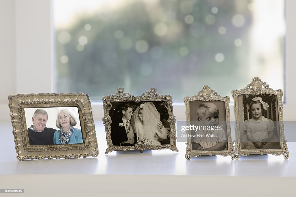 row of framed photos spanning a lifetime : Stock Photo