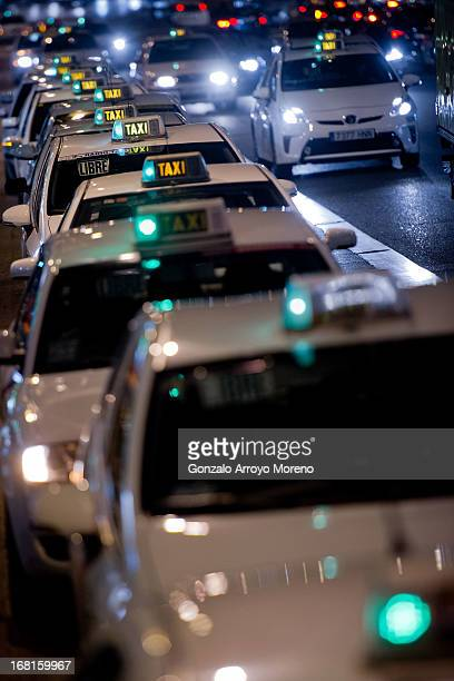 A row of free taxis waits for potential clients as a musical finishes at a theatre on Gran Via street on April 23 2013 in Madrid Spain According to...