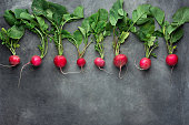 Row of Fresh Raw Organic Red Radishes with Green Leaves Arranged in Upper Row Border on Dark Concrete Stone Background. Copy Space for Text. Website Banner Poster Template. Vegetarian Supefoods