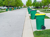 Row of garbage bins lined up along the roadside in a neat urban suburb waiting to be collected for disposal of the rubbish