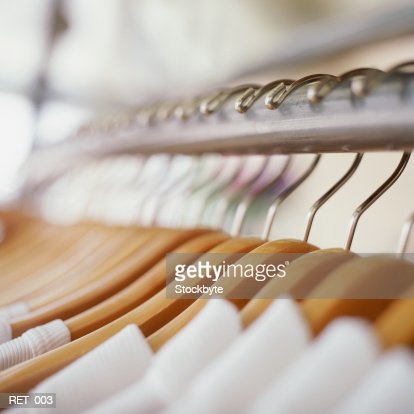 Row of garments on wooden hangers : Stock Photo