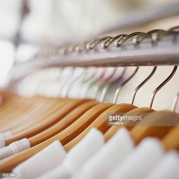 Row of garments on wooden hangers