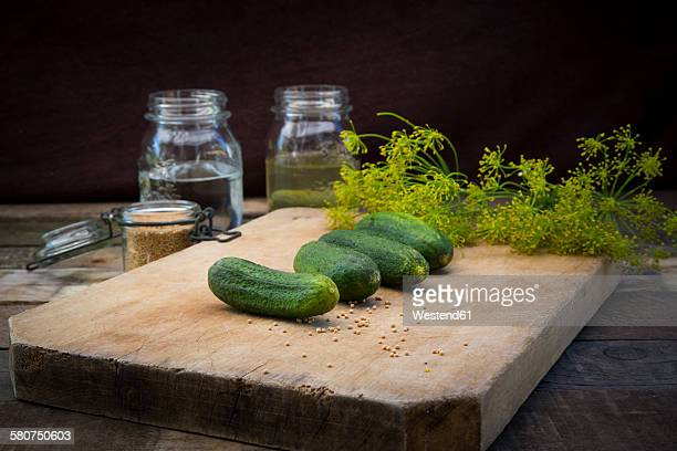Row of gherkins on wooden board