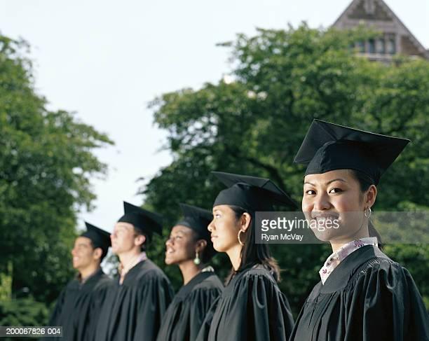 Row of graduates, focus on female graduate smiling