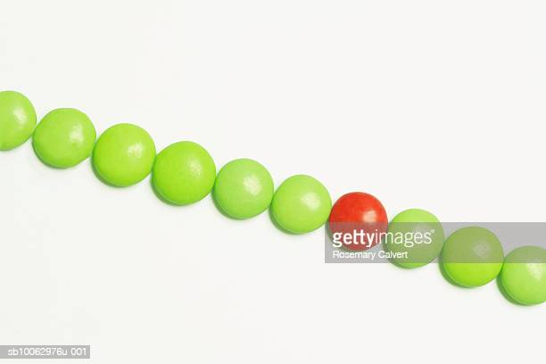 Row of green candy coated chocolate sweets with one red in middle, overhead view