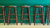 Row of wooden stools in front of green counter inside a vintage style bar.