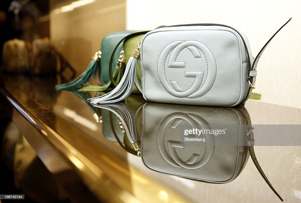 A row of Gucci 'Soho' bags bearing the interlocking 'G' logo are reflected in a glass display shelf inside a Gucci store, a luxury unit of France's PPR SA, in Rome, Italy, on Monday, Nov. 19, 2012. PPR SA, the French owner of the Gucci and Puma brands, said it's confident of revenue and profit growth in 2012. Photographer: Alessia Pierdomenico/Bloomberg via Getty Images